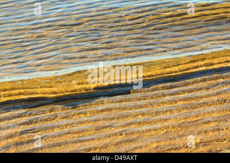 Eine kleine Welle rollt sanft in den Sandstrand - Stockfoto