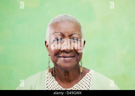 Alte schwarze Frau Portrait, Dame in eleganter Kleidung lächelnd auf grünem Hintergrund. Textfreiraum - Stockfoto