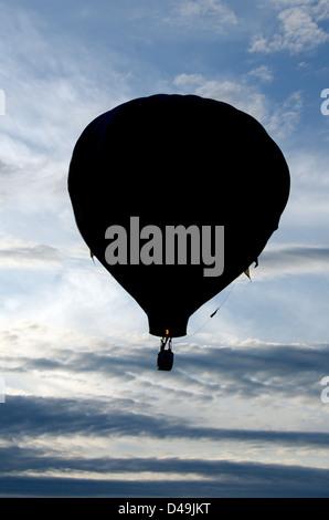 Ein Heißluftballon ist vor einem blauen Himmel gefüllt mit geschwollenen weißen Wolken Silhouette. - Stockfoto