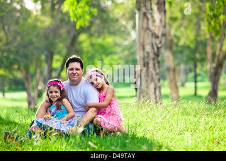 Vater und Töchter auf Picknick - umarmt beim Sitzen - Stockfoto