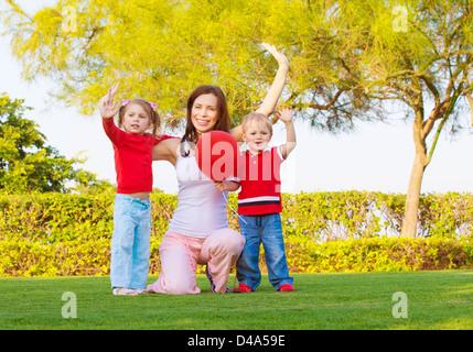 Foto von hübschen Mutter mit zwei niedlichen Kinder erhobenen Hände hoch und genießen Sonnentag, glückliche junge - Stockfoto