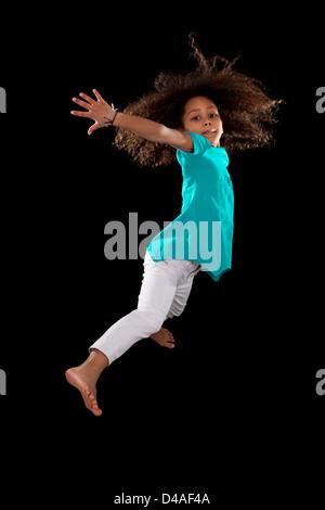 Porträt von cute Young African American Mädchen springen über schwarzem Hintergrund - Stockfoto