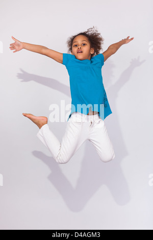 Porträt von cute Young African American Mädchen springen über grauen Hintergrund - Stockfoto