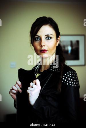 Junge Frau trägt eine beschlagene Lederjacke in Rock Chick Stil Mode mit Haaren zurück gekehrt der 20er Jahre - Stockfoto