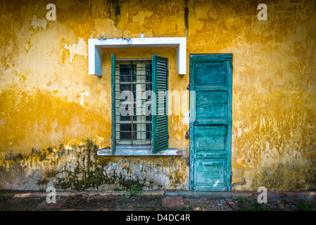 Außenansicht des verlassenen Hauses mit Details in Vietnam. Alt und schäbig gelbe Wand mit Fenster und abgenutzte - Stockfoto