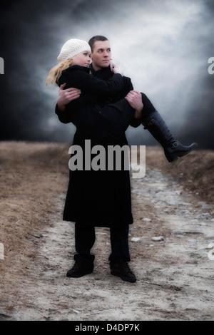 ein Mann trägt seine Freundin über eine Wiese - Stockfoto