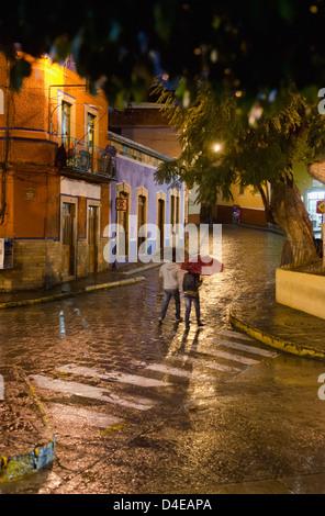 Mexiko, Guanajuato, Guanajuato, Passanten mit Sonnenschirmen am regnerischen Abend - Stockfoto