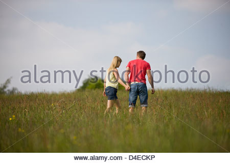 Ein junges Paar hand in hand gehen durch ein Feld im Sommer - Stockfoto