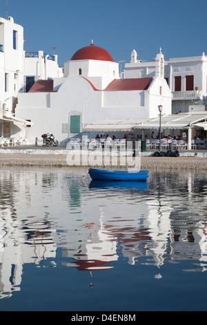 Weiße Kirche mit roter Kuppel, Café im Freien, blaues Boot und Reflexionen im Hafen von Mykonos - Stockfoto