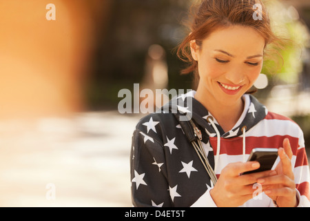 Frau mit Handy auf Stadtstraße - Stockfoto