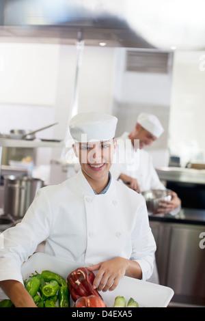 Koch mit Wanne mit Gemüse in der Küche des Restaurants - Stockfoto