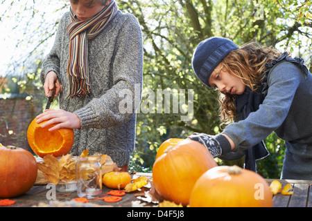 Kinder schnitzen Kürbisse zusammen im freien - Stockfoto