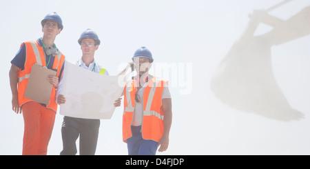 Arbeitnehmer, die Baupläne vor Ort lesen - Stockfoto