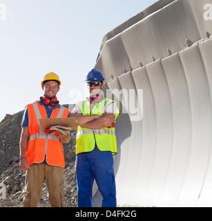 Arbeitnehmer, die lächelnd von Maschinen im Steinbruch - Stockfoto