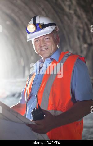 Geschäftsmann Lesung Blaupausen in tunnel - Stockfoto