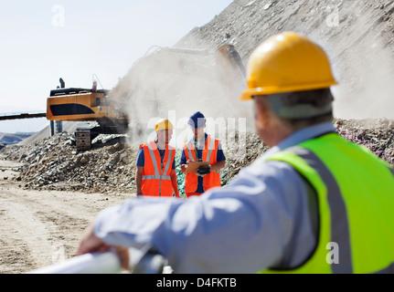 Geschäftsmann beobachten Arbeiter im Steinbruch - Stockfoto