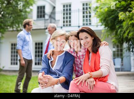 Familie lächelnd zusammen vor Haus - Stockfoto