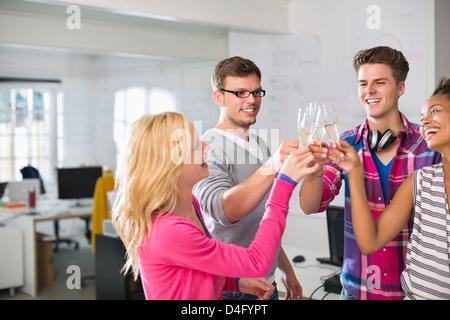 Business-Leute Toasten gegenseitig mit Champagner im Büro - Stockfoto