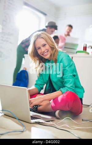 Geschäftsfrau mit Laptop im Stock im Büro - Stockfoto