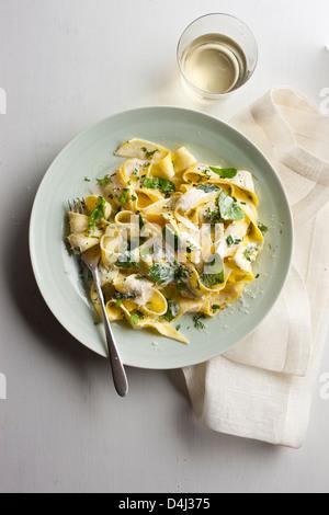 Ein Teller mit Pappardelle Pasta mit cremigem Ricotta, Baby-Spinat, frischen Kräutern und Pfeffer.