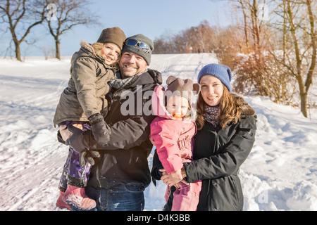 Familie lächelnd zusammen im Schnee - Stockfoto