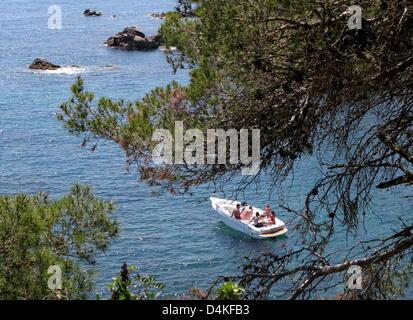 Ein Boot mit Touristen im Bild vor der Küste nahe der Stadt Calella de Palafrugell an der Costa Brava, Spanien, - Stockfoto