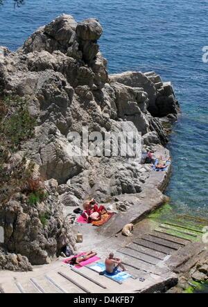 Touristen liegen in der Sonne an der felsigen Küste nahe der Stadt Calella de Palafrugell an der Costa Brava, Spanien, - Stockfoto