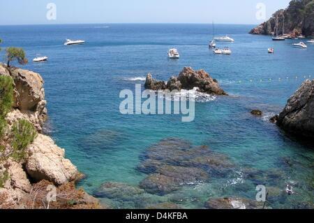 Yachten und Segelboote im Bild vor der felsigen Küste in der Nähe der Stadt Calella de Palafrugell an der Costa - Stockfoto