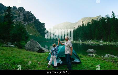 Vater und Sohn pitching Zelt zusammen - Stockfoto