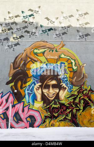Wandbild oder Graffiti an der Wand in Tromsø, Norwegen, Darstellung von fliegenden Kühen und eine Figur mit Sonnenbrille - Stockfoto