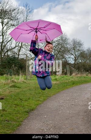 8 Jahre alte kaukasische Mädchen Spaß springen mit einem rosa Regenschirm im Park - Stockfoto