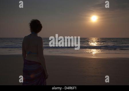 Eine Frau blickt auf das Meer, wie die Sonne am Nachmittag. Setzen Sie auf Arossim Beach, Süd-Goa, Indien. - Stockfoto