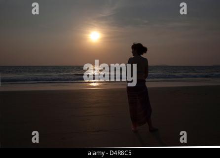 Setzen Sie auf Arossim Beach, Süd-Goa, Indien. Eine Frau blickt auf das Meer, wie die Sonne am Nachmittag. - Stockfoto