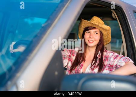 Junge Frau in Cowgirl Outfit fahren eine Pickup-Truck, Weiblich 19 kaukasischen, Texas, USA - Stockfoto