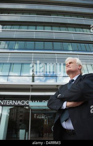 Reife Geschäftsmann vor Bürogebäude mit Armen gefaltet - Stockfoto
