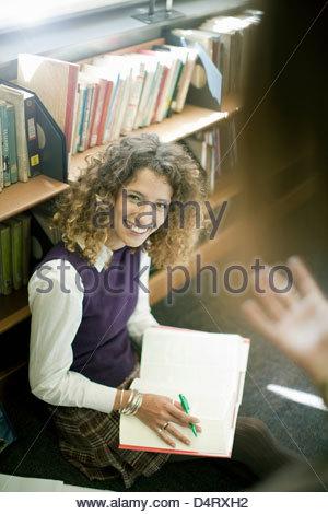 Student lächelnd in Bibliothek - Stockfoto