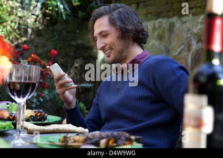 Mann mit Handy am Tisch im freien - Stockfoto
