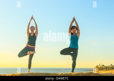 Frauen praktizieren Yoga auf Felsformation - Stockfoto