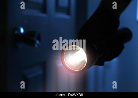 Schattenhafte männlichen Eindringling hält eine Fackel oder Taschenlampe in einem dunklen Raum. - Stockfoto