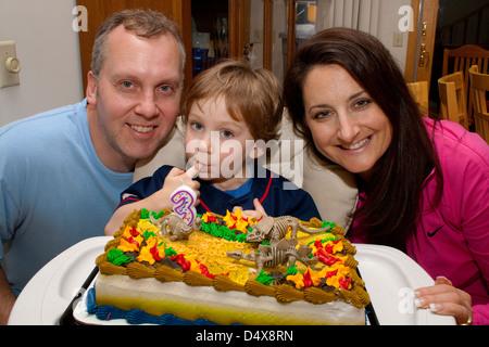Eltern (Alter 43) jungen dekoriert Alter 3 feiert seinen Geburtstag mit Dinosaurier Kuchen. Mahtomedi Minnesota - Stockfoto