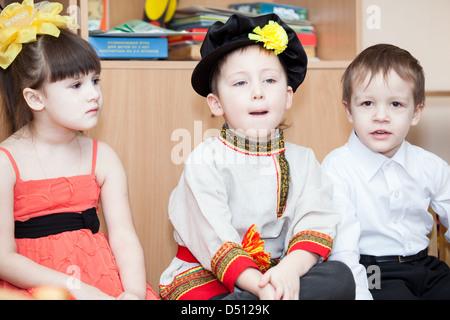 Süsser Boy in russische traditionelle Kleidung im Kindergarten sitzen auf Stühlen im Klassenzimmer. Russland - Stockfoto