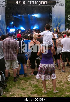 Ein kleiner Junge zu seiner Mutter Schultern gerade ein Konzert auf dem Festival d'ete de Quebec - Stockfoto