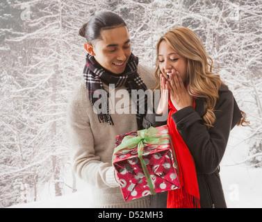 Mann die Freundin Geschenk im Schnee - Stockfoto