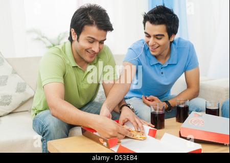 Freunde teilen Pizza und lächelnd zu Hause - Stockfoto