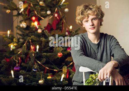 Teenager sitzen Weihnachtsbaum - Stockfoto