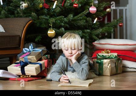 Junge schreiben unter Weihnachtsbaum - Stockfoto