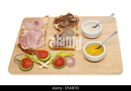 Rindfleisch und Schinken belegte Brötchen mit Salat, Senf und Meerrettich Sauce auf einem Holzbrett isoliert gegen - Stockfoto