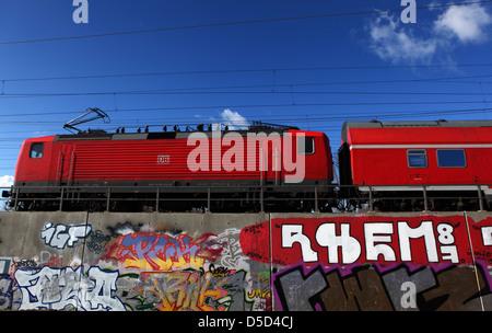 Berlin, Deutschland, regionale Straßenbahn fährt über eine mit Graffiti-Bahnlinie besprüht - Stockfoto