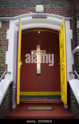 Ein Jesus rettet Neon-Schild am Eingang einer evangelischen Kirche in Peckham, Südlondon. Die gelbe Türen an der - Stockfoto