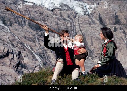 Der Sohn eines jungen norwegischen Paares Tracht versucht ein Vintage Holz Alphorn, die Neverlur in Fjærland, Norwegen - Stockfoto